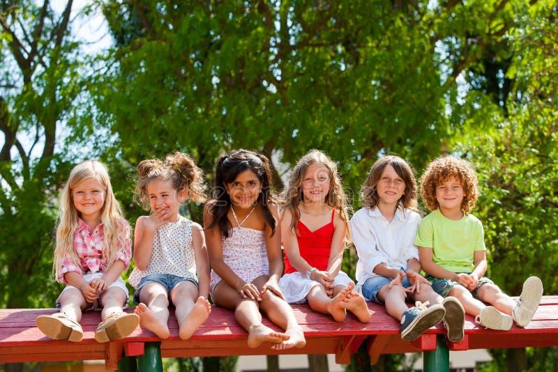六个孩子一起坐屋顶在公园。 库存图片