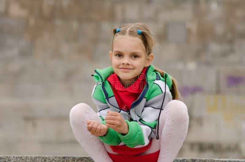 六岁的女孩在花岗岩墙壁的背景蹲下了 免版税图库摄影