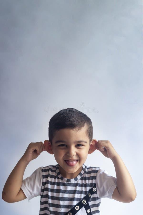 六年男孩画象 无辜微笑灰色背景的小男孩 小男孩歪曲他的面孔 人们,童年生活方式 免版税库存照片