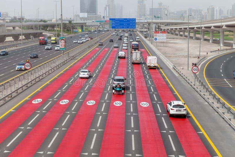 六车道高速高速公路和到商业中心移动汽车的小河  限速是一百km每个小时 免版税库存图片