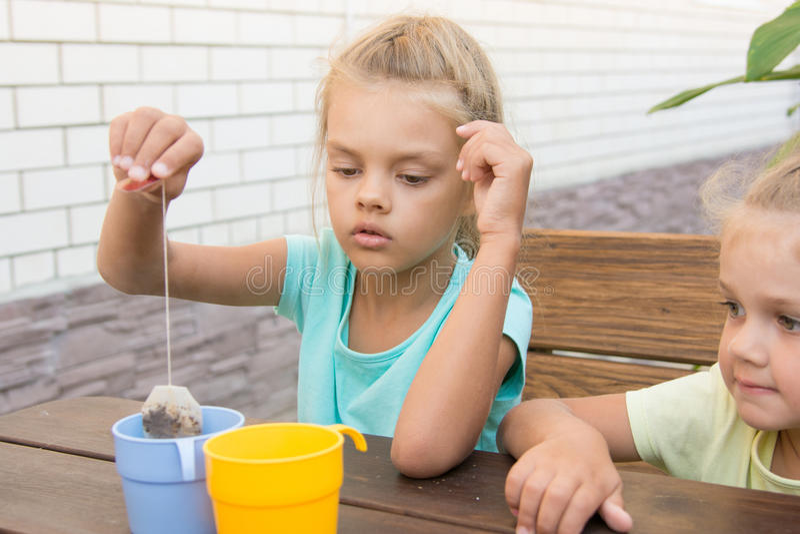 六年的女孩酿造一杯茶从袋子的 免版税库存照片