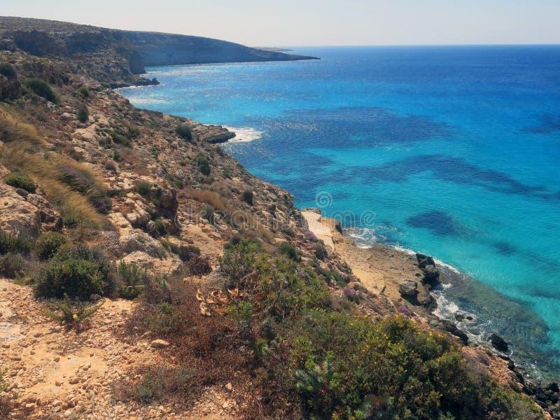 兰佩杜萨在有峭壁的意大利和清洗蓝色海 库存图片
