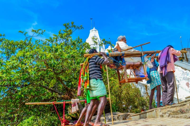 兰契,贾坎德邦,印度, 2017年:搬运工在一个多小山区域搭载在轿子安装的一个游人对古庙PARESHNAT 免版税图库摄影