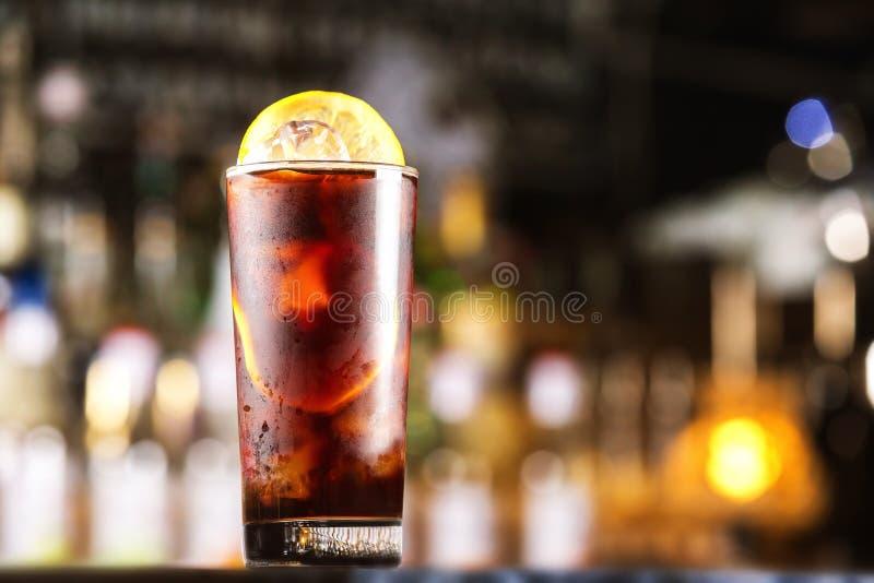 兰姆酒与冰块的可乐在欢乐酒吧的鸡尾酒和柠檬站立 免版税库存图片