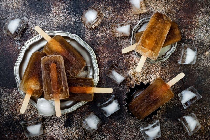 兰姆酒和焦炭鸡尾酒冰棍儿用柠檬汁 古巴libre自创结冰的酒精paletas -冰流行 顶上,平的位置 免版税库存图片