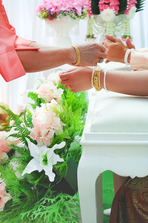 兰纳螺纹拉紧或泰国样式婚礼领带仪式,新娘的手栓与从年长妇女的白色螺纹 库存照片