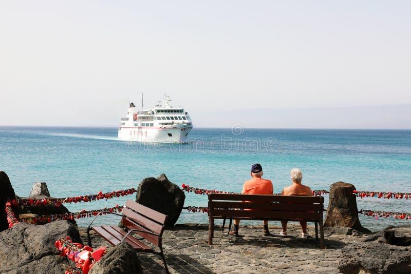 兰萨罗特岛,西班牙- 2018年4月18日:资深游人夫妇坐看对一艘大船的长凳来在Playa布朗卡 免版税库存照片