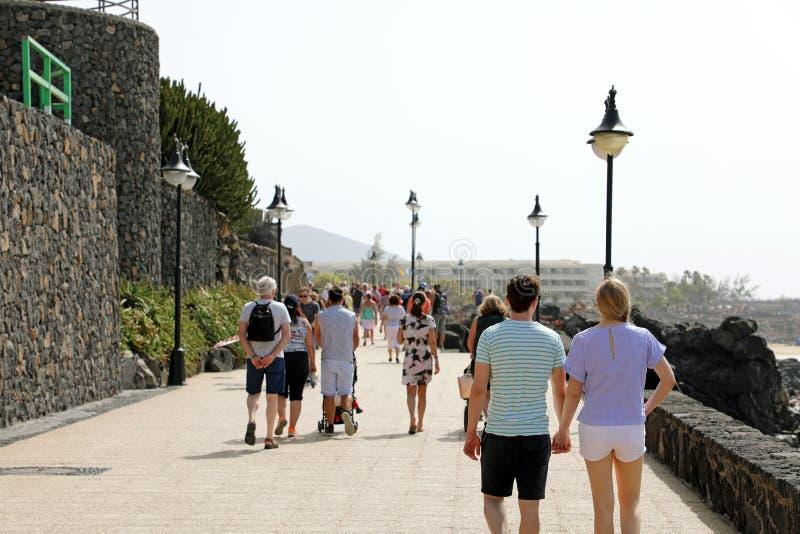 兰萨罗特岛,西班牙- 2018年4月18日:走在Playa布朗卡的游人散步,兰萨罗特岛,加那利群岛,西班牙 免版税库存图片
