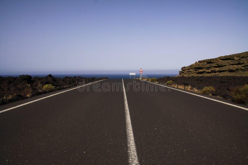 兰萨罗特岛- Timanfaya NP:驾驶在不尽的空的柏油路的旅行在贫瘠风景的黑熔岩岩石之间到大西洋 库存照片