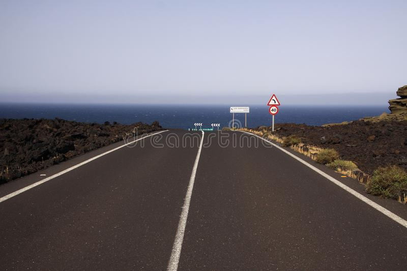 兰萨罗特岛- Timanfaya NP:驾驶在不尽的空的柏油路的旅行在贫瘠风景的黑熔岩岩石之间到大西洋 免版税图库摄影