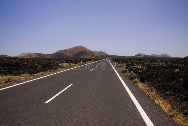 兰萨罗特岛- Timanfaya NP:驾驶在不尽的空的柏油路的旅行在贫瘠风景的黑熔岩岩石之间 免版税库存图片