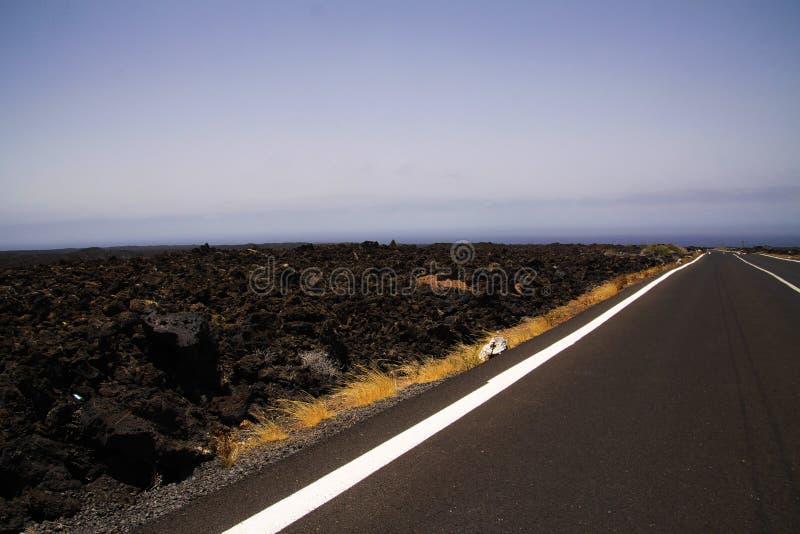 兰萨罗特岛- Timanfaya NP:驾驶在不尽的空的柏油路的旅行在贫瘠风景的黑熔岩岩石之间 库存图片