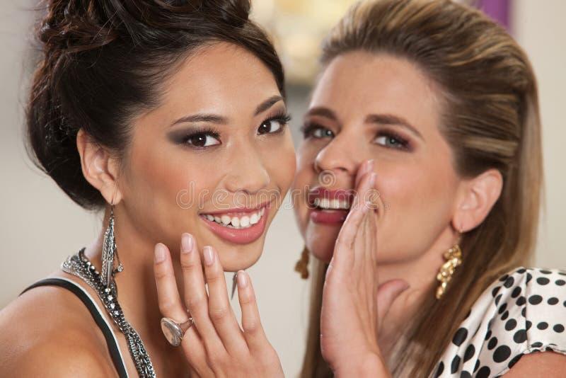 共享秘密的微笑的朋友 免版税库存图片