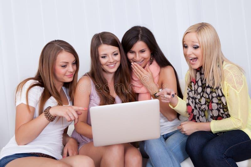 共享膝上型计算机的长沙发的妇女 免版税库存图片