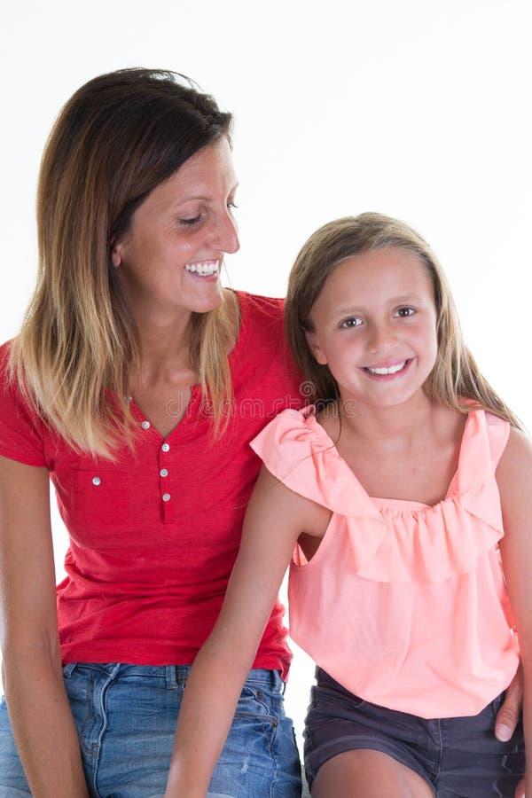 共谋和爱照顾女儿白色背景的秀丽女孩 库存照片