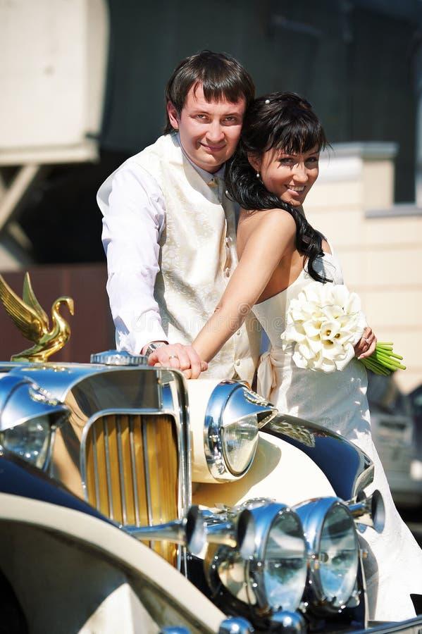 关于减速火箭的大型高级轿车的愉快的新郎和新娘 免版税库存图片