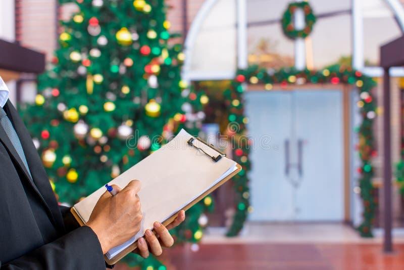 关于剪贴板的人笔记在圣诞树,新年2019年,礼物,h 免版税库存照片