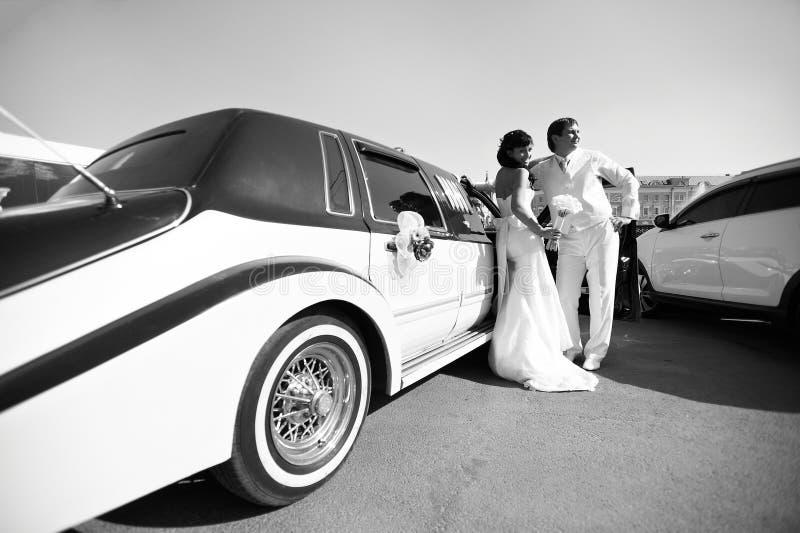 关于大型高级轿车的愉快的新娘和新郎 免版税库存图片