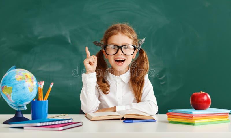 关于学校黑板的滑稽的儿童女小学生女生 免版税库存图片