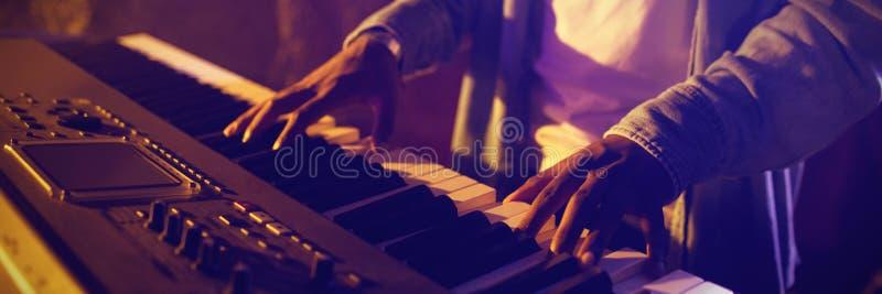 关于弹钢琴的男性音乐家的中间部分 免版税库存图片