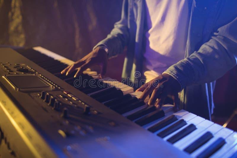 关于弹钢琴的男性音乐家的中间部分 库存照片