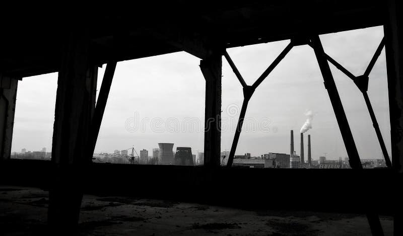 从关于抽烟的烟窗的被放弃的工厂车间看 免版税库存照片