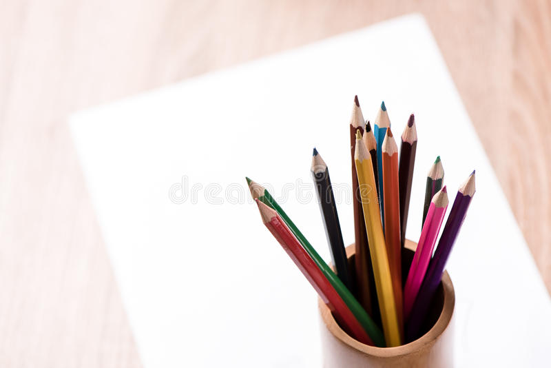 关于木桌的色的铅笔和纸笔记 免版税库存照片