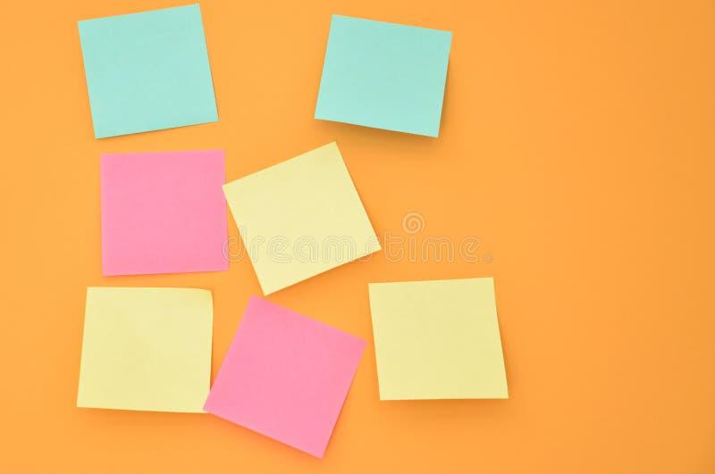 关于橙色墙壁的便条纸 免版税图库摄影