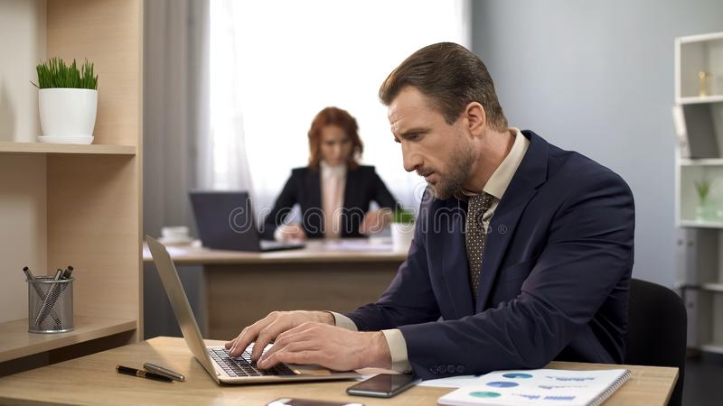 关于膝上型计算机的办公室经理键入的数据,完成的项目,满意对结果 图库摄影