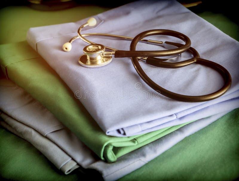 关于蓝色的听诊器和绿色在医院护理制服 库存照片
