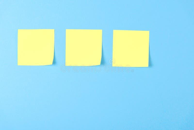 关于蓝色背景的空白黄色稠粘的笔记,企业工作的概念 在蓝色墙壁上的黄色备忘录贴纸 r 免版税库存照片