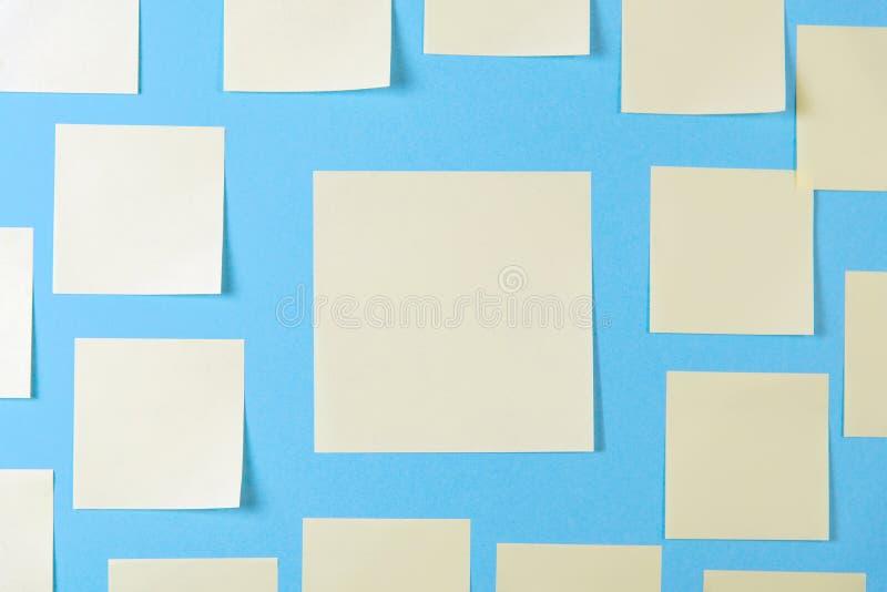 关于蓝色背景的空白黄色稠粘的笔记,企业工作的概念 在蓝色墙壁上的黄色备忘录贴纸 r 库存图片