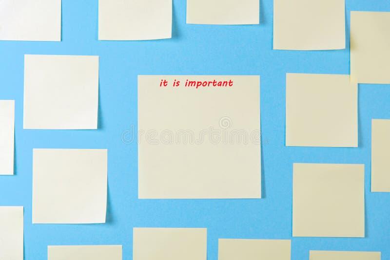 关于蓝色背景的空白黄色稠粘的笔记,企业工作的概念 在蓝色墙壁上的黄色备忘录贴纸 r ?treadled 免版税库存图片