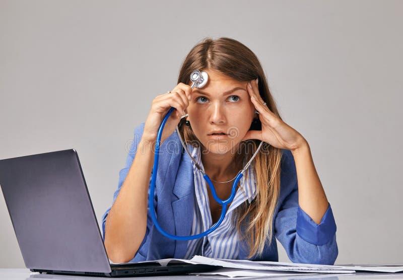关于问题的概念在工作 一名女工,向上看,听使用phonendoscope的她自己 免版税库存图片