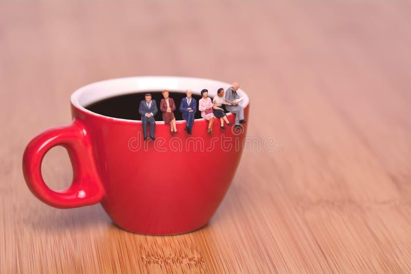 关于饮用的咖啡和等待的创造性的概念 杯子的微型人 免版税图库摄影