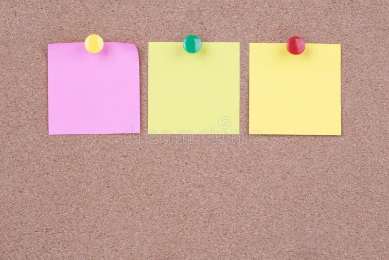 关于黄柏板的五颜六色的稠粘的纸笔记 免版税库存照片