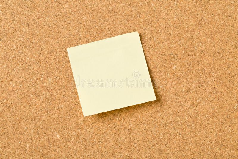 关于黄柏板的空的黄色稠粘的纸备忘录笔记 免版税库存图片