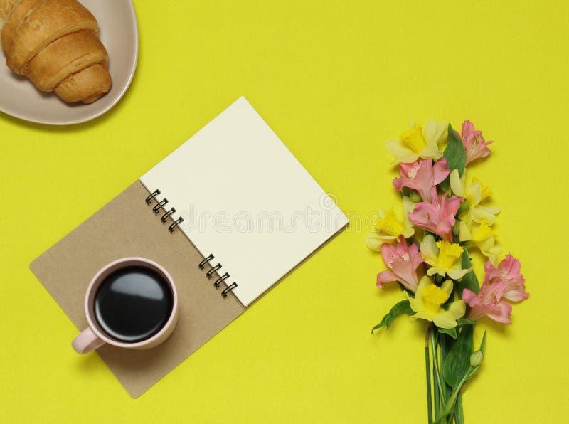关于黄色背景与花,咖啡的纸笔记,新月形面包 免版税库存图片