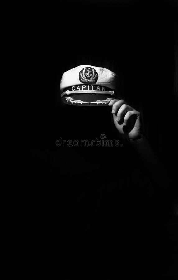关于captain's帽子和一只手的概念性图象在黑暗 免版税库存照片