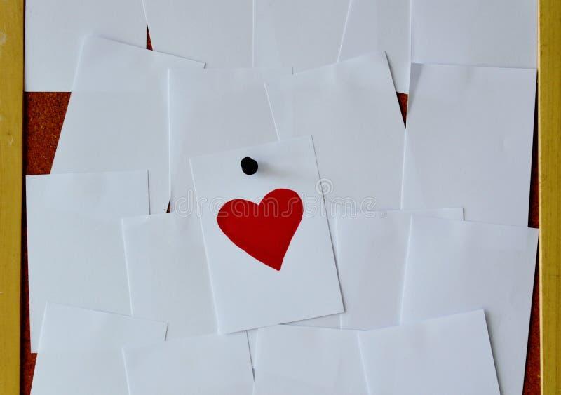关于noticeboard的红色心脏纸笔记 图库摄影