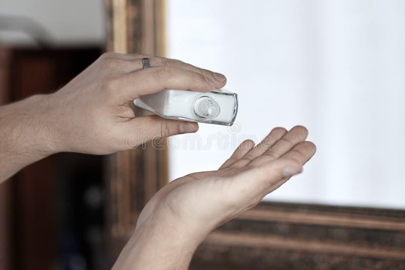关心与润肤液的人手,落下从瓶 在卫生间里,帅哥每日惯例  图库摄影
