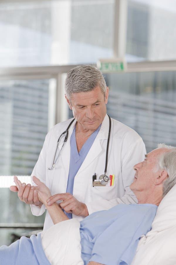 关心医生男性耐心采取 免版税库存照片