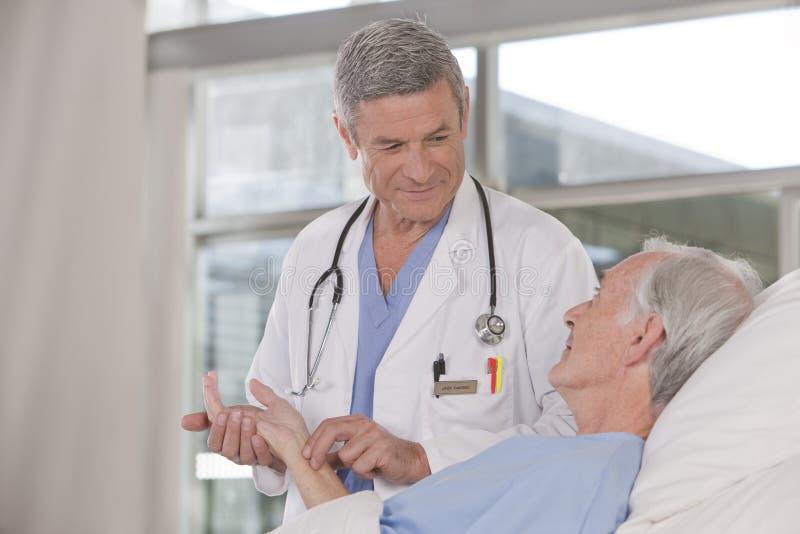 关心医生男性耐心采取 免版税图库摄影