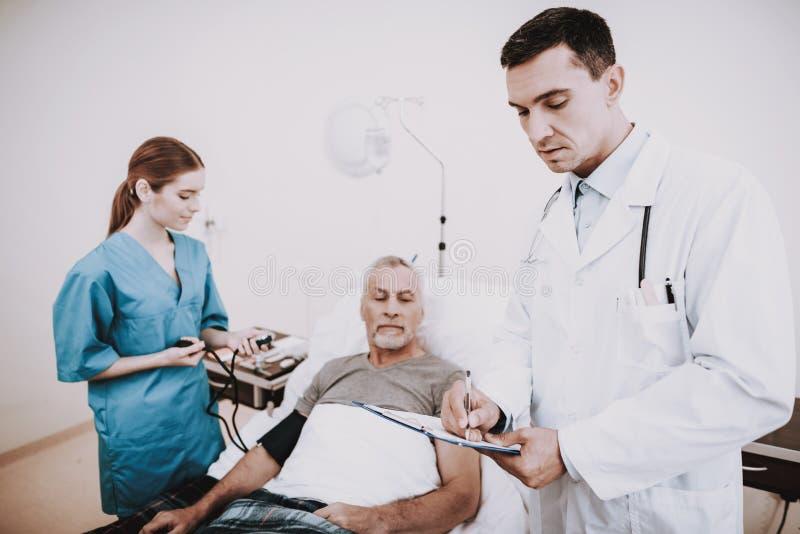 关心医生 老人在有医生的绝尘室 免版税库存图片