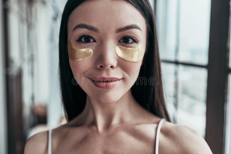关心她皮肤采取 使用眼睛patche的可爱的少妇 免版税库存图片