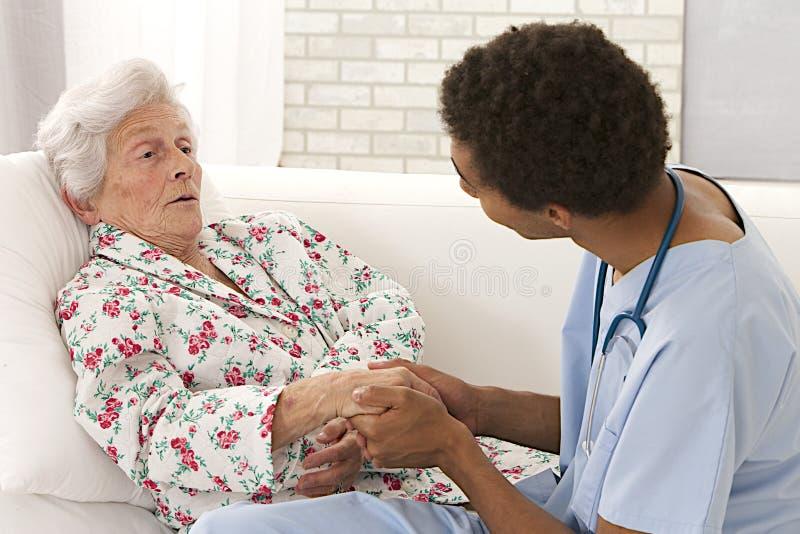 关心对一名非常老女性患者的年轻混血儿医生 免版税库存照片