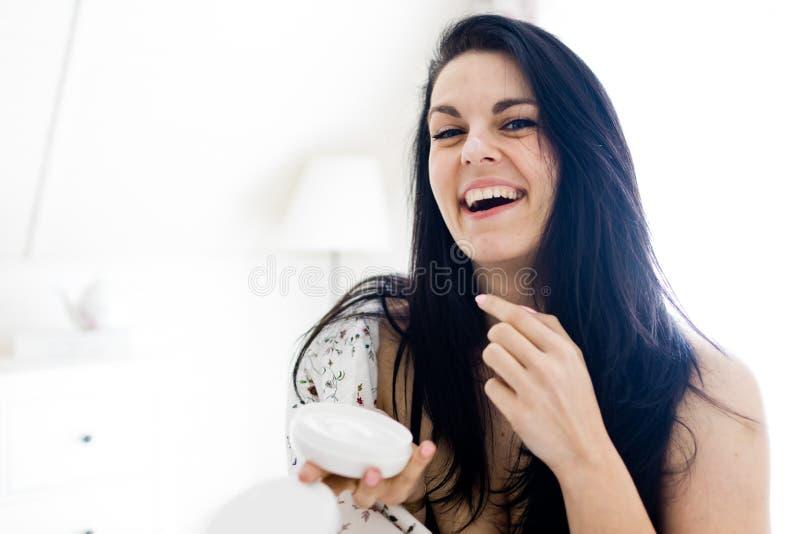 关心对她的与润湿的化妆水-巨大心情的皮肤的美丽的年轻女人 免版税图库摄影