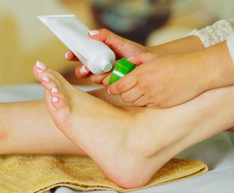 关心对她的脚和把水合的奶油放的妇女在它上与奶油色瓶 库存照片