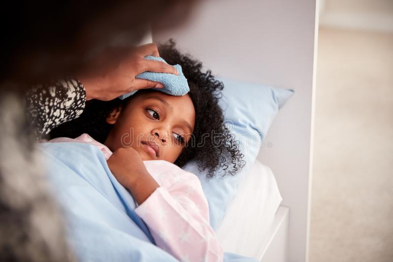 关心对病态的女儿不适的母亲在床上与温度 免版税库存照片