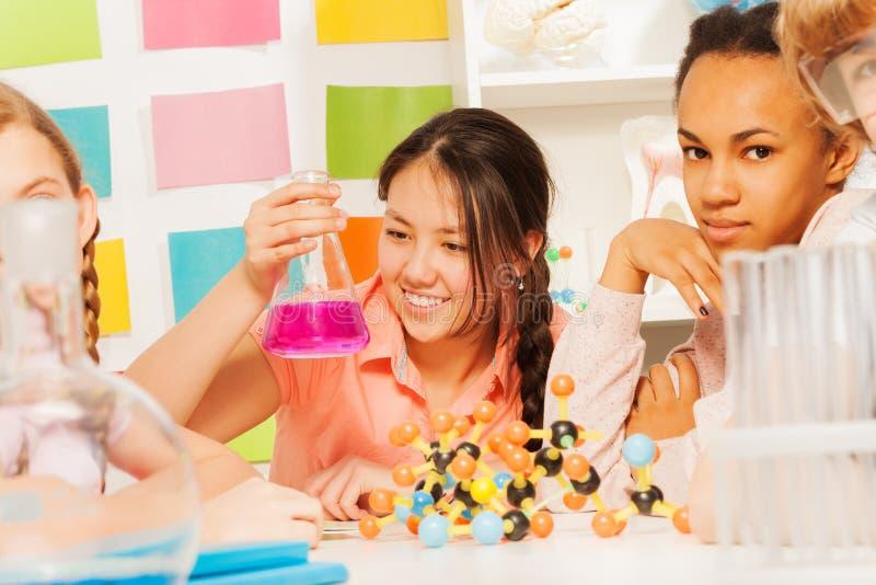 关心少年的学生在实验室里试验 免版税图库摄影